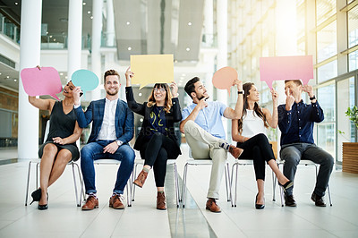 Buy stock photo Shot of a group of businesspeople holding colorful speech bubbles while sitting in line