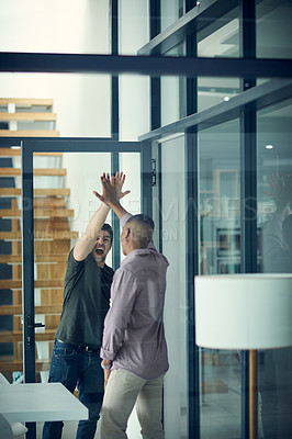 Buy stock photo Shot of two young businessmen giving each other a high five in a modern office
