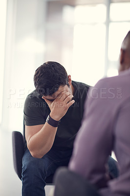 Buy stock photo Shot of an unhappy young man talking with a colleague