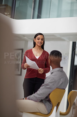Buy stock photo Shot of a young businesswoman and businessman going over paperwork together in a modern office