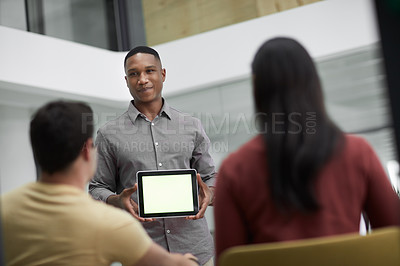 Buy stock photo Shot of a young businessman using a digital tablet during a meeting with colleagues in a modern office