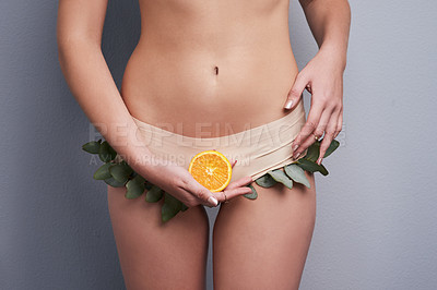 Buy stock photo Cropped studio shot of a woman wearing leafy underwear and holding an orange against a grey background