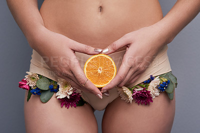 Buy stock photo Cropped studio shot of a woman wearing floral underwear and holding an orange against a grey background