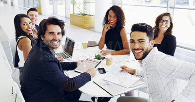 Buy stock photo Cropped shot of a group of businesspeople sitting around the boardroom table during a meeting