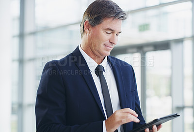 Buy stock photo Cropped shot of a mature businessman using a digital tablet while walking through a modern office