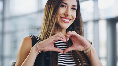 Buy stock photo Cropped shot of a young businesswoman showing a heart sign while walking through a modern office