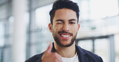 Buy stock photo Cropped shot of a young businessman showing winking and showing thumbs up while walking through a modern office