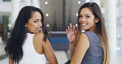 Buy stock photo Cropped shot of two young businesswomen waving while walking in a modern office