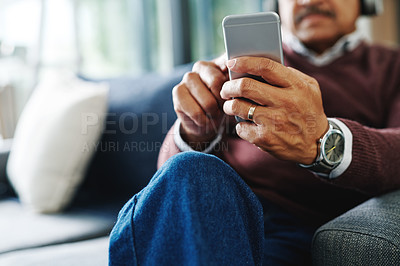 Buy stock photo Cropped shot of a mature man using his cellphone while relaxing at home