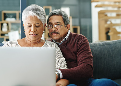 Buy stock photo Shot of a mature couple using a laptop while relaxing at home