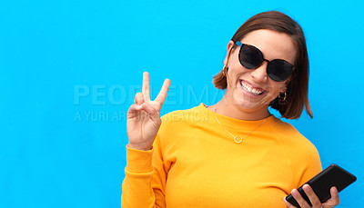 Buy stock photo Cropped portrait of a happy young woman showing the peace sign against a blue background