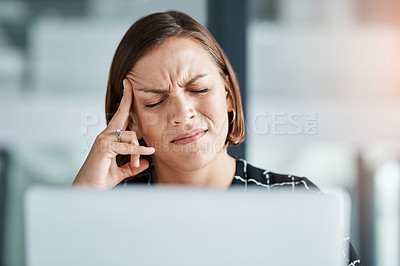Buy stock photo Cropped shot of a young businesswoman suffering with a headache while working in an office