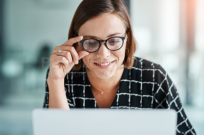 Buy stock photo Cropped shot of a happy young businesswoman working on a laptop in an office