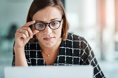 Buy stock photo Cropped shot of a young woman working on a laptop in an office
