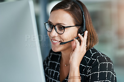 Buy stock photo Cropped shot of a happy young call centre agent working on a computer in an office