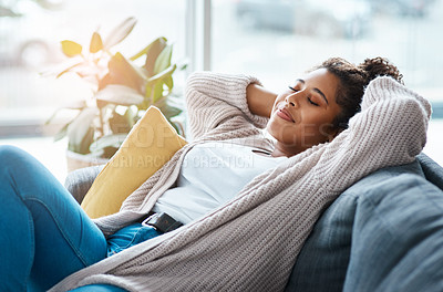Buy stock photo Cropped shot of an attractive young woman relaxing on her couch at home