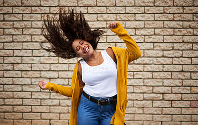 Buy stock photo Cropped shot of a happy young woman dancing against a brick wall