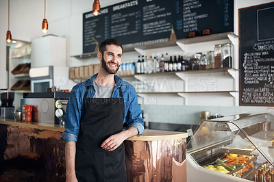 Buy stock photo Shot of a young business owner standing in his coffee shop