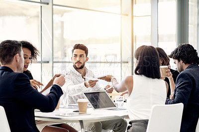 Buy stock photo Shot of a group of businesspeople passing around paperwork during a meeting in an office