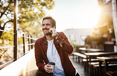 Buy stock photo Cropped shot of a handsome young man talking on his cellphone while drinking a coffee outside
