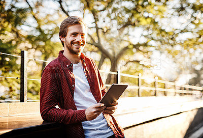 Buy stock photo Cropped portrait of a handsome young man using his digital tablet outside