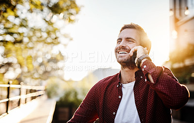 Buy stock photo Cropped shot of a handsome young man talking on his cellphone outside