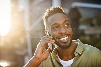 Buy stock photo Cropped shot of a handsome young man using his cellphone while standing outside
