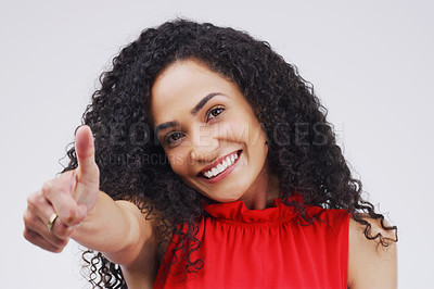 Buy stock photo Studio portrait of an attractive young woman giving a thumbs up against a grey background