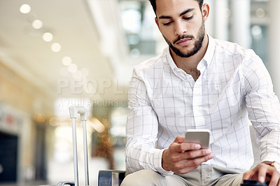 Buy stock photo Shot of an unrecognizable businessman texting on his phone and drinking coffee while waiting for his flight at the airport