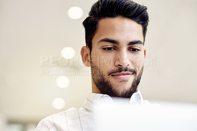 Buy stock photo Shot of a focused young businessman working on his laptop while waiting for his flight at the airport