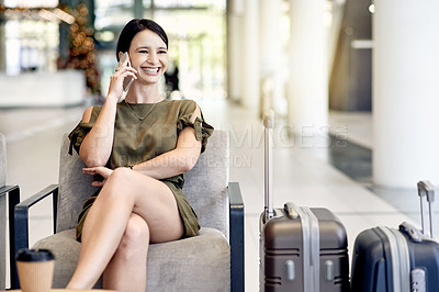 Buy stock photo Shot of a cheerful young businesswoman calling on her cellphone while waiting for her flight at a airport