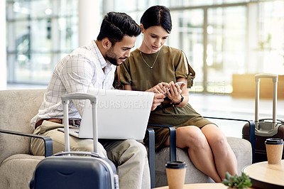 Buy stock photo Shot of a two focussed young businesspeople working on a laptop together while waiting for their flight at a airport