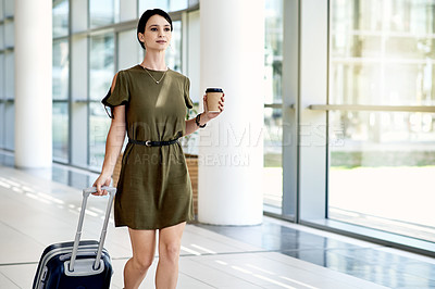 Buy stock photo Shot of a confident young businesswoman walking with a coffee and dragging her luggage inside of a airport during the day