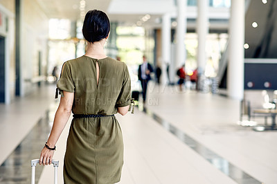 Buy stock photo Rearview shot of a confident young businesswoman walking with a digital tablet and dragging her luggage inside of a airport during the day