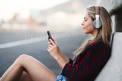 Buy stock photo Shot of an attractive young woman sitting down and listening to music on her cellphone in the city