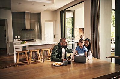 Buy stock photo Shot of a young family of three using a digital tablet together at home