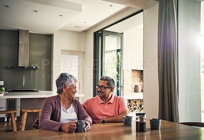 Buy stock photo Shot of a mature couple chatting and having coffee together at home