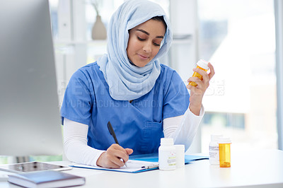 Buy stock photo Cropped shot of an attractive young female doctor using a digital tablet to double-check medication while sitting in her office in the hospital
