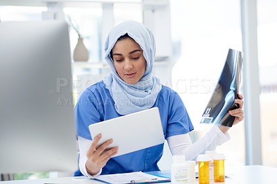 Buy stock photo Cropped shot of an attractive young female doctor comparing a physical x ray to the one on her digital tablet while sitting in her office in the hospital