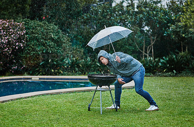 Buy stock photo Shot of a young man having a barbecue outside in the rain