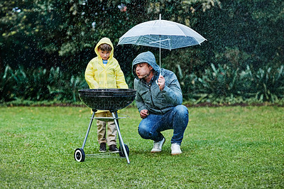 Buy stock photo Shot of a little boy and his father having a barbecue outside in the rain