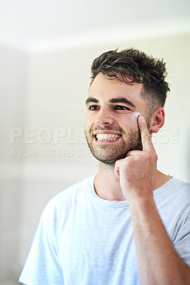 Buy stock photo Shot of a young man applying moisturizer to his face in the bathroom at home