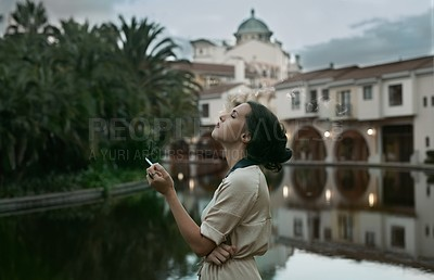 Buy stock photo Cropped shot of an attractive young woman smoking a cigarette next to a lake in an urban setting