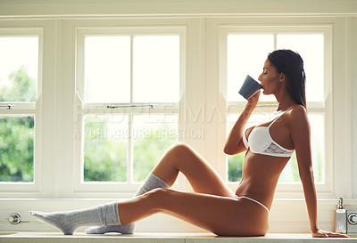 Buy stock photo Shot of an attractive young woman in lingerie drinking coffee while sitting on the kitchen counter at home