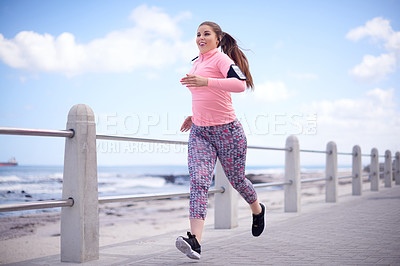 Buy stock photo Full length shot of an attractive and sporty young woman running along the promenade