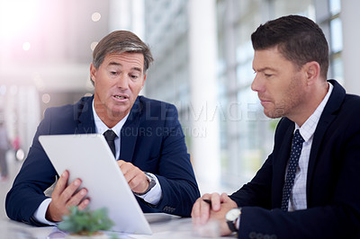 Buy stock photo Cropped shot of two businessmen discussing work over a tablet in the boardroom