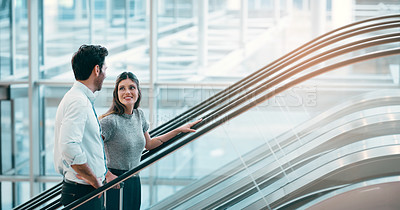 Buy stock photo Cropped shot of two businesspeople talking while on an escalator in the workplace