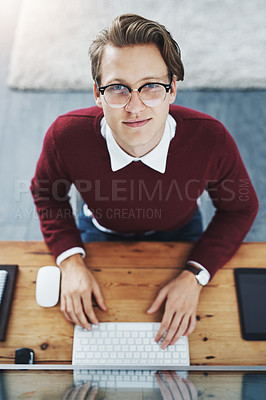 Buy stock photo High angle shot of a young man using a computer at his desk in a modern office