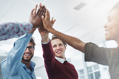 Buy stock photo Shot of a team of young go getters giving each other a high five in a modern office