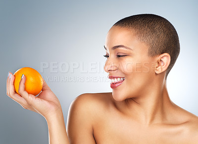 Buy stock photo Studio shot of a beautiful young woman posing with an orange against a grey background